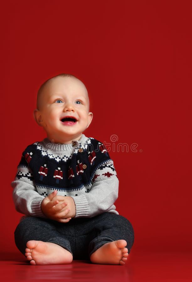 Funny little baby wearing warm knitted Christmas sweater at studio on cold winter day. royalty free stock photo