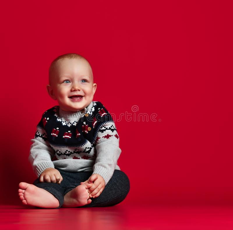 Funny little baby wearing warm knitted Christmas sweater at studio on cold winter day. stock images