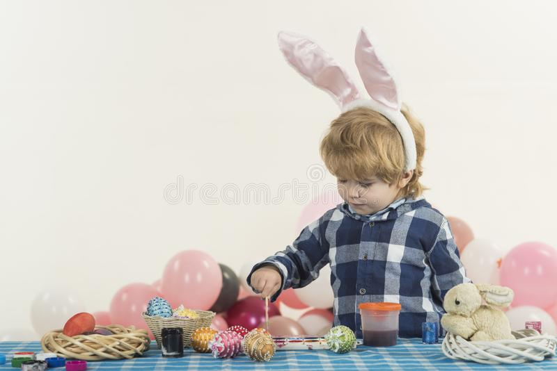 Funny little boy with bunny ears and colorful Easter eggs. Easter holiday. Colouring eggs for eastertime at home. Happy royalty free stock photos