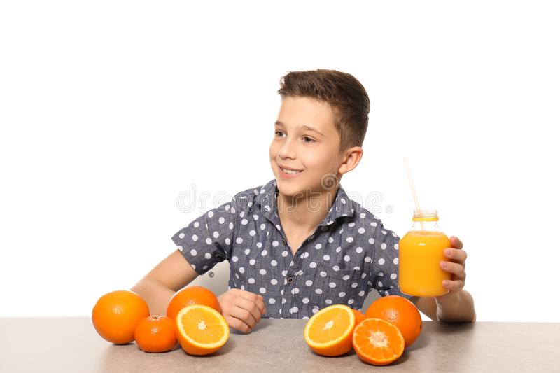 Funny little boy with citrus fruit and juice sitting at table against white background stock photo