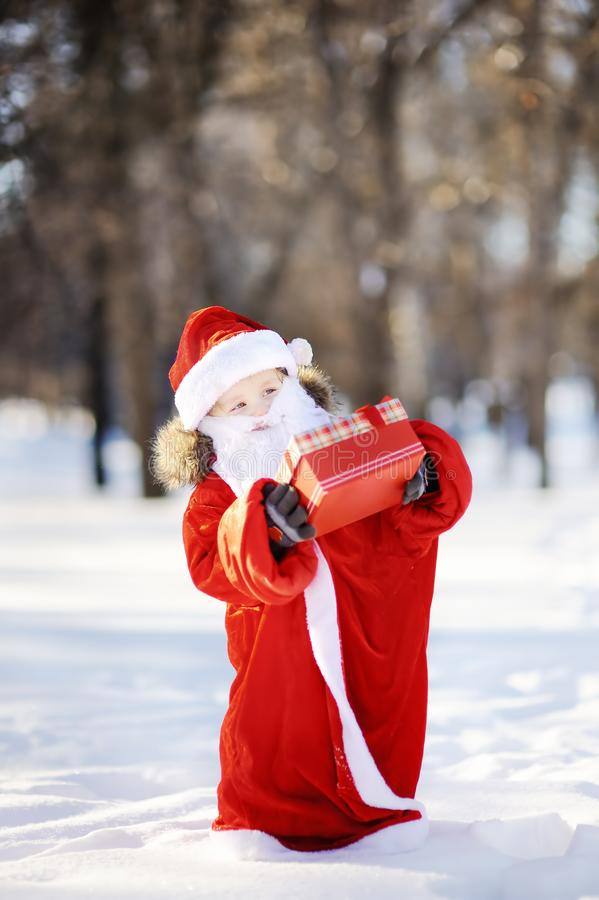 Funny little boy dressed like Santa Claus holding red box with Christmas gift royalty free stock photography