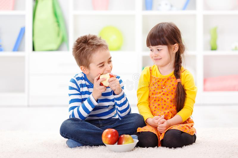 Funny little boy eating apple royalty free stock photo