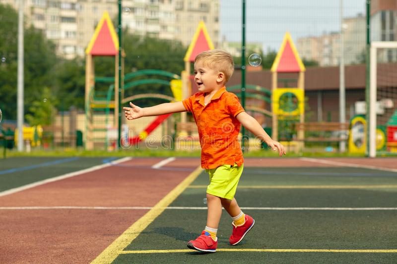 Funny little boy on playground. playing child. On sports ground royalty free stock photos