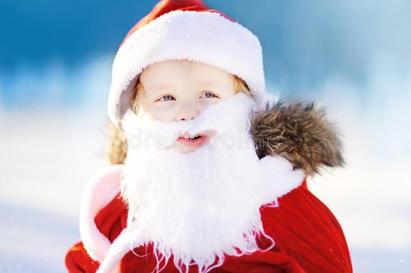 Funny little boy wearing Santa Claus costume in winter snowy park stock photography