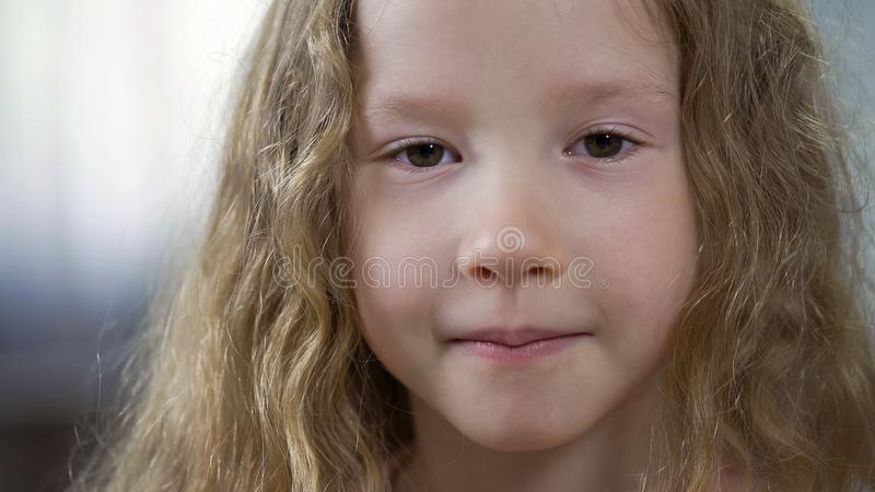 Funny little Caucasian girl looking to camera, childhood concept, face close-up stock photography