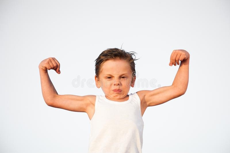 Funny little caucasian kid with grimace on his face showing biceps muscle stock photos
