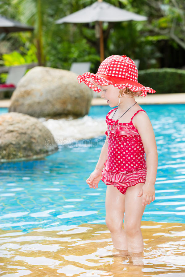 Funny little child girl near swimming pool on tropical resort in Thailand, Phuket. Summer vacations and sport concept royalty free stock photo