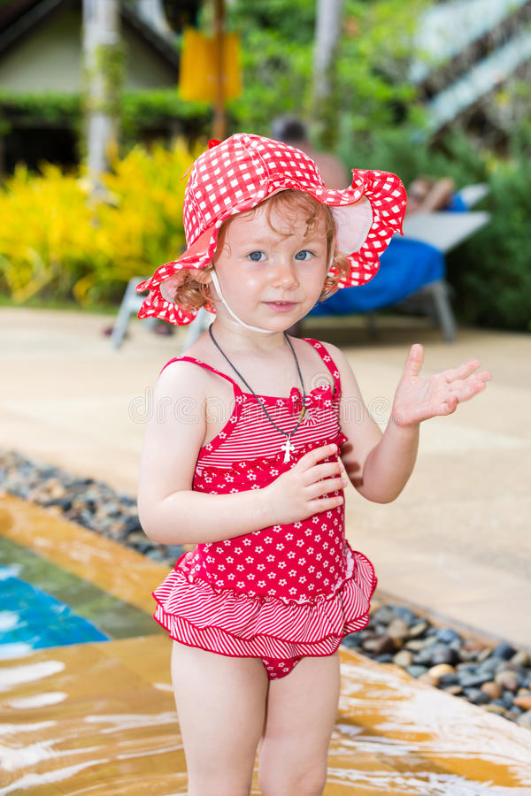 Funny little child girl near swimming pool on tropical resort in Thailand, Phuket. Summer vacations and sport concept royalty free stock images