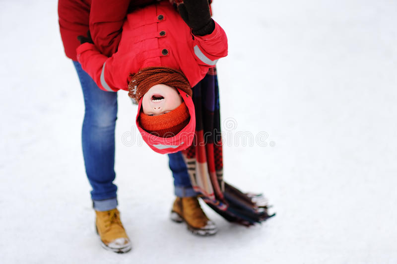 Funny little child and his mother havnig fun in snowy park stock photos