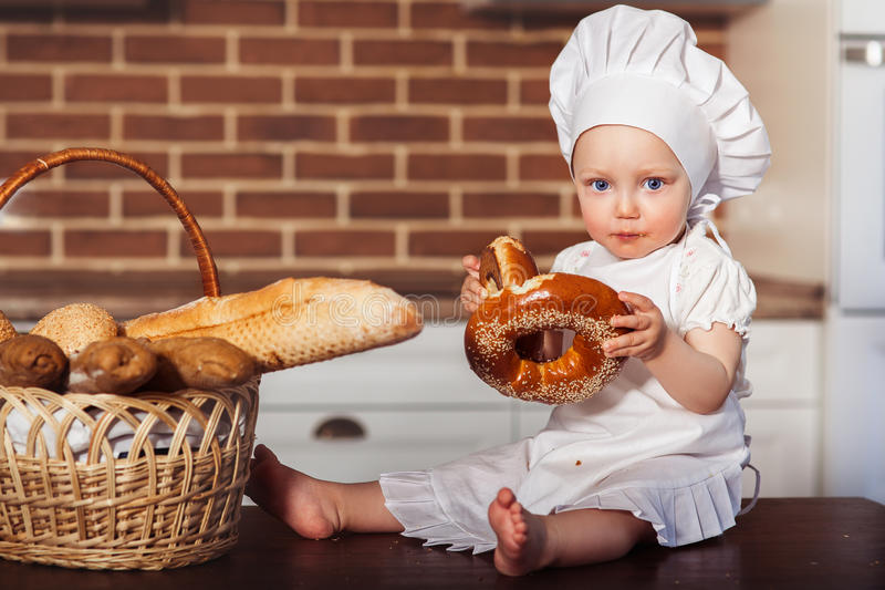 Funny little cook in kitchen with bakery. Scullion eating a bagel royalty free stock images