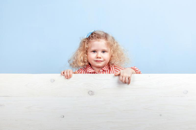 Funny little curly girl in a striped red and white dress and blue flower on her hair stands behind the wooden board royalty free stock image