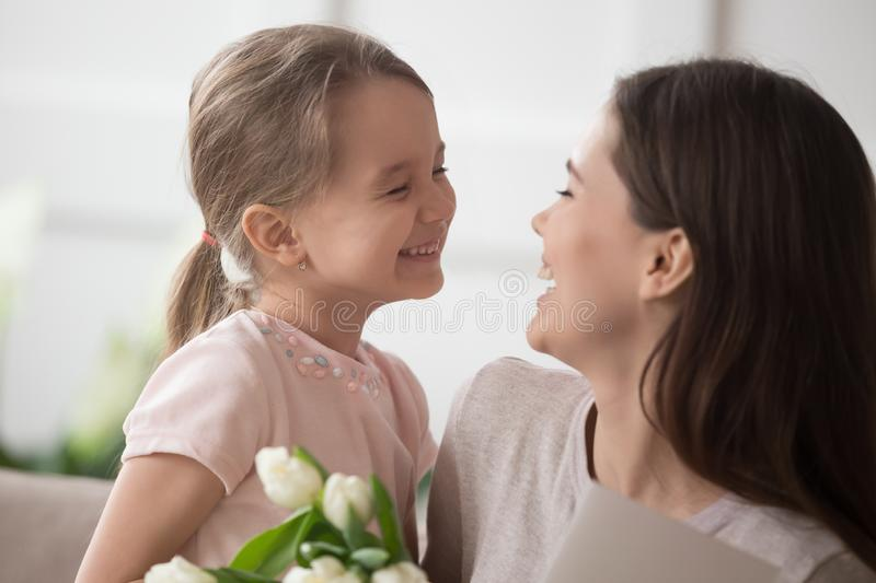 Funny little daughter have fun laughing greeting mom stock photo