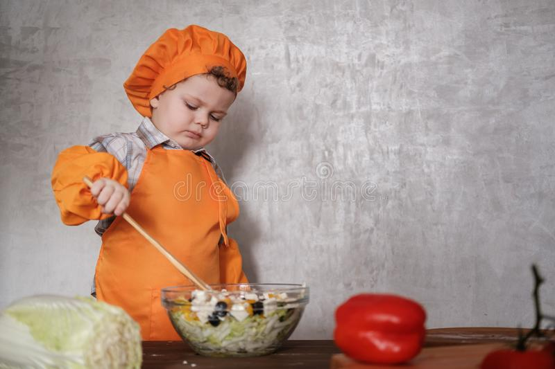Funny little European boy dressed like a chef mixes a Greek salad with a spoon. In a bowl on a background of gray wall royalty free stock images