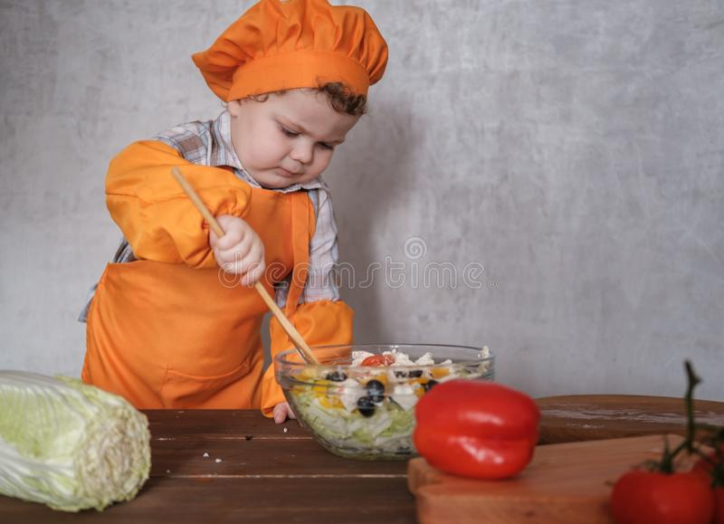 Funny little European boy dressed like a chef mixes a Greek salad with a spoon. In a bowl on a background of gray wall royalty free stock image