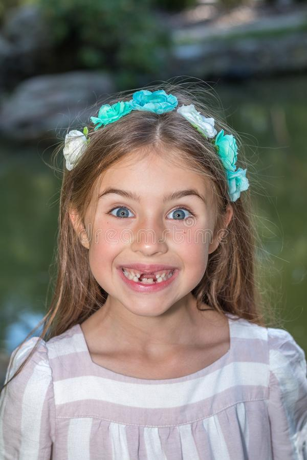 Funny little girl's portrait. Funny portret of little girl who lost front teeth. City park in the summer time royalty free stock image