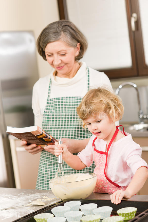 Funny little girl baking cupcake with grandma. Funny little girl baking cupcake with grandmother hold whisk stock image