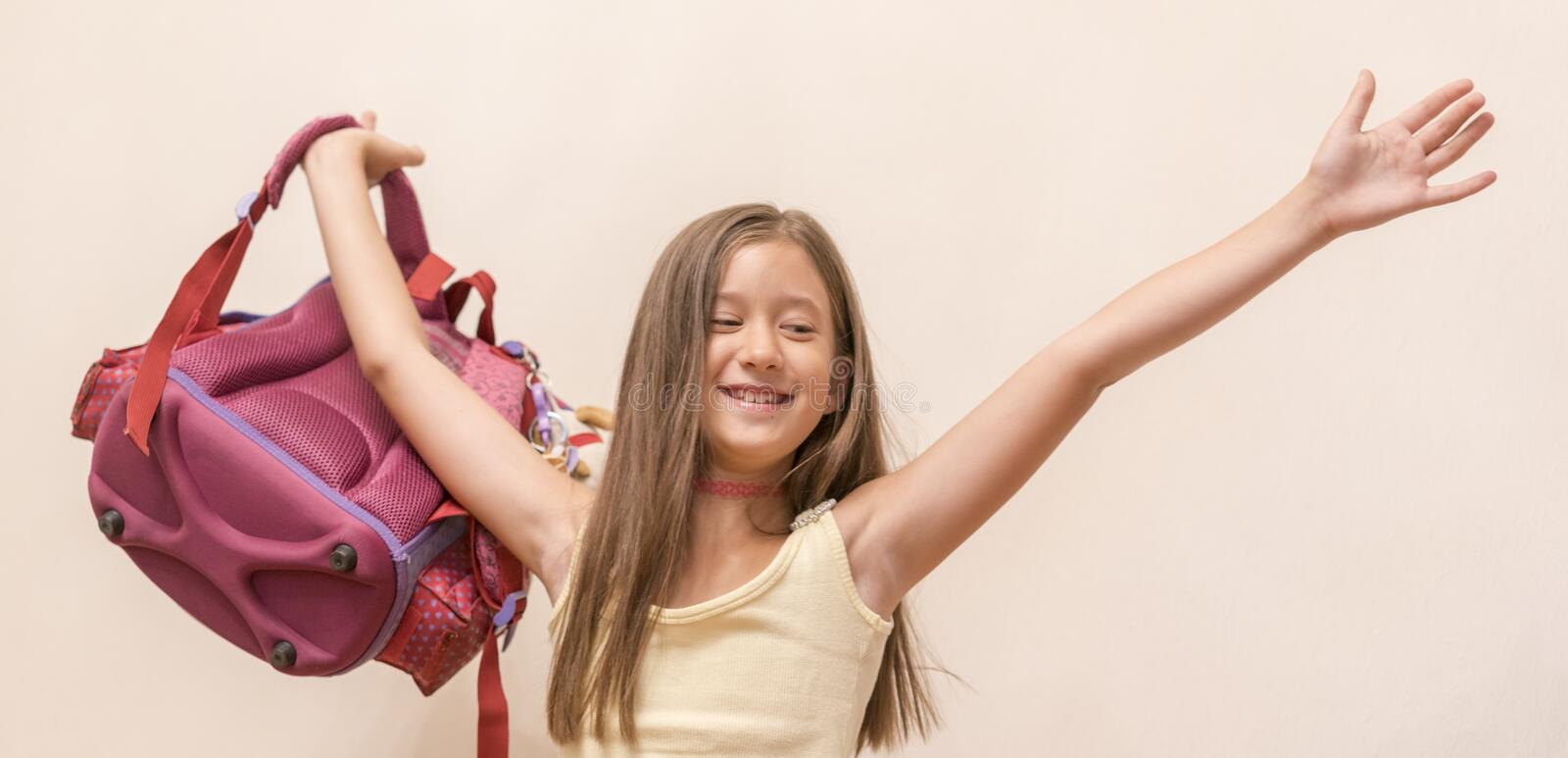 Funny little girl with big backpack jumping and having fun against white wall. School concept. Back to School. School& x27;s out royalty free stock photo