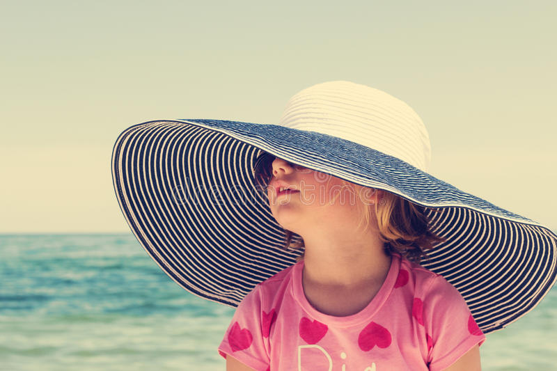 Funny little girl in a big striped hat on the beach. royalty free stock photography