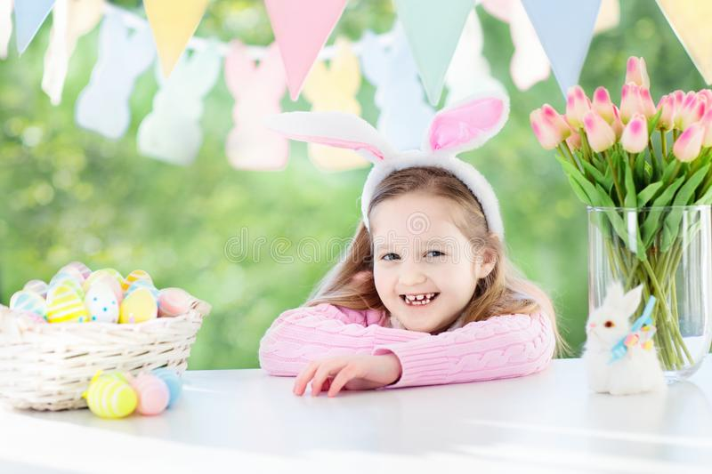 Funny little girl in bunny ears with Easter eggs. Funny little girl in bunny ears at breakfast on Easter morning at table with Easter eggs basket. Kids stock photography