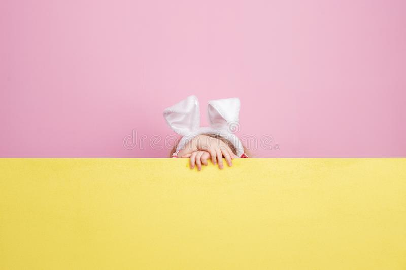 Funny little girl with bunny ears on her head hides behind the yellow board against a pink wall royalty free stock image