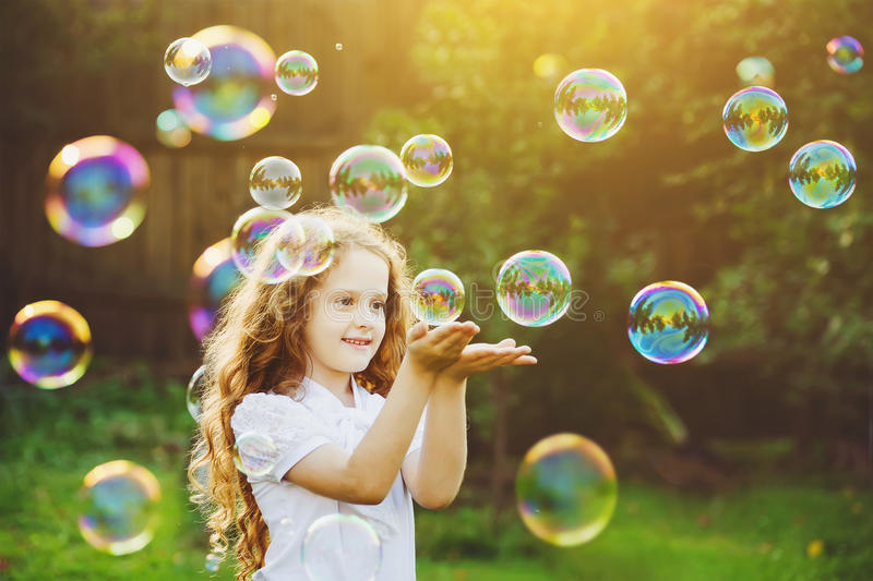 Funny little girl catching soap bubbles in the summer on nature. stock photography
