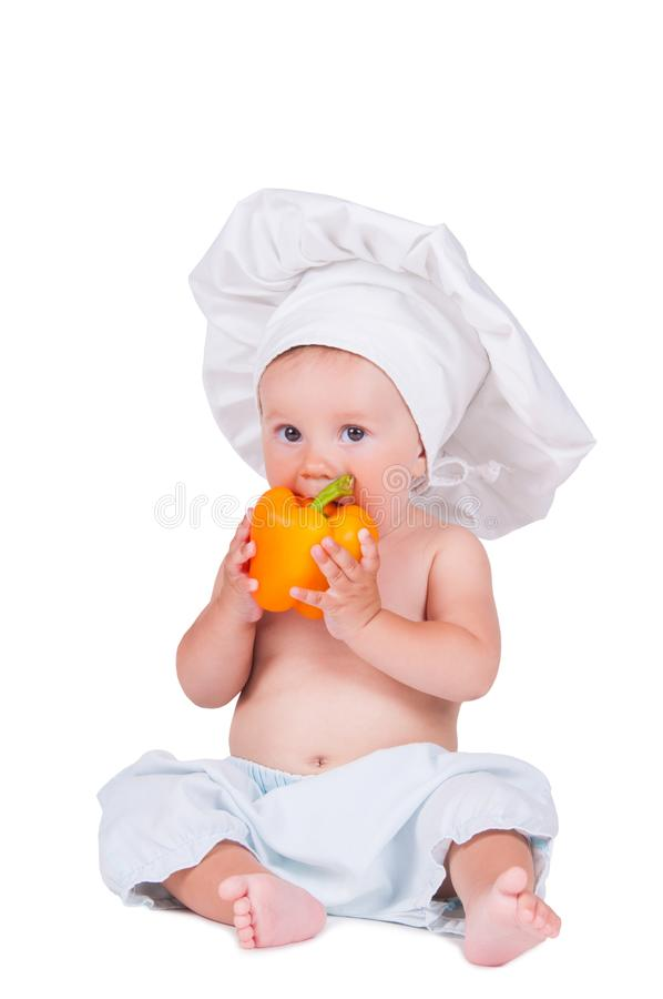 A funny little girl in a chef`s clothes is eating pepper. royalty free stock photo