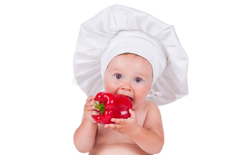 A funny little girl in a chef`s clothes is eating pepper. stock photos