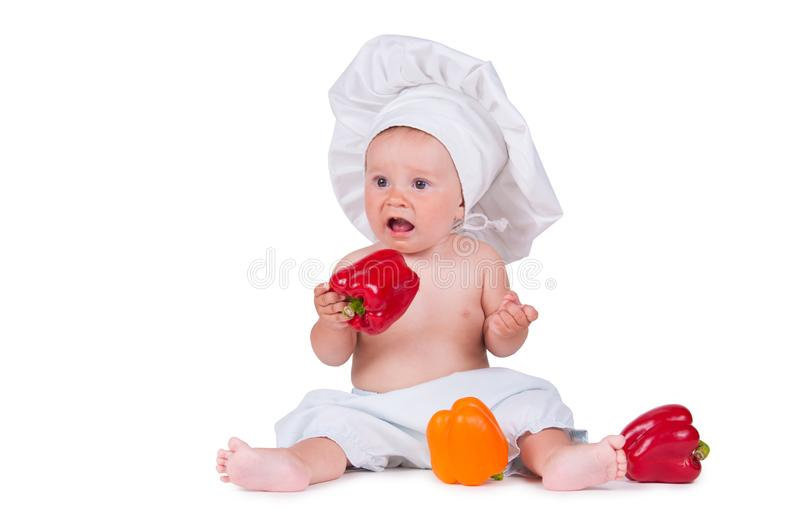 A funny little girl in a chef`s clothes is eating pepper. royalty free stock image