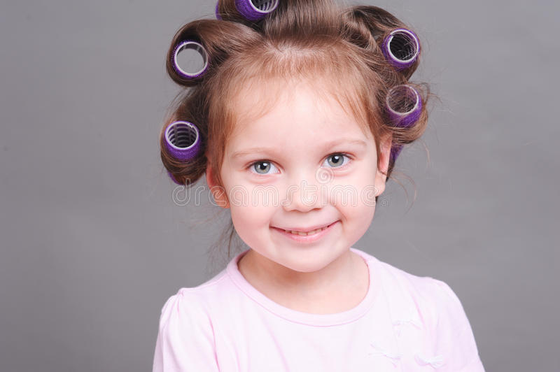 Funny little girl with curlers stock image
