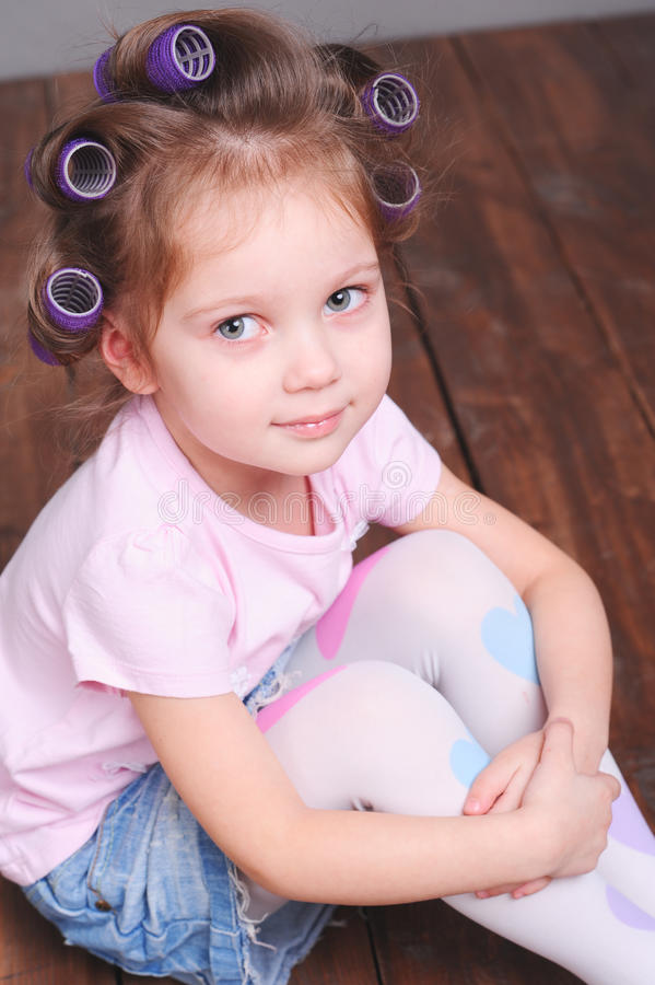 Funny little girl with curlers royalty free stock image