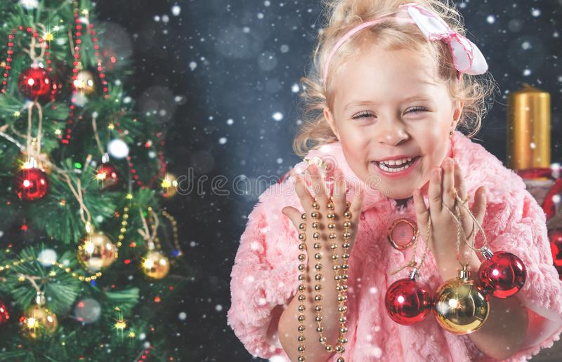 Funny little girl decorating Christmas tree stock images