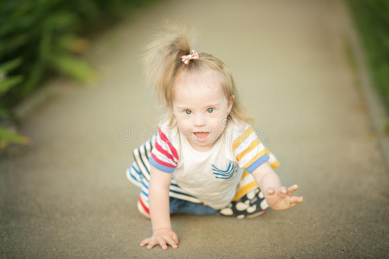 Funny little girl with Down syndrome creeps along the path stock photos