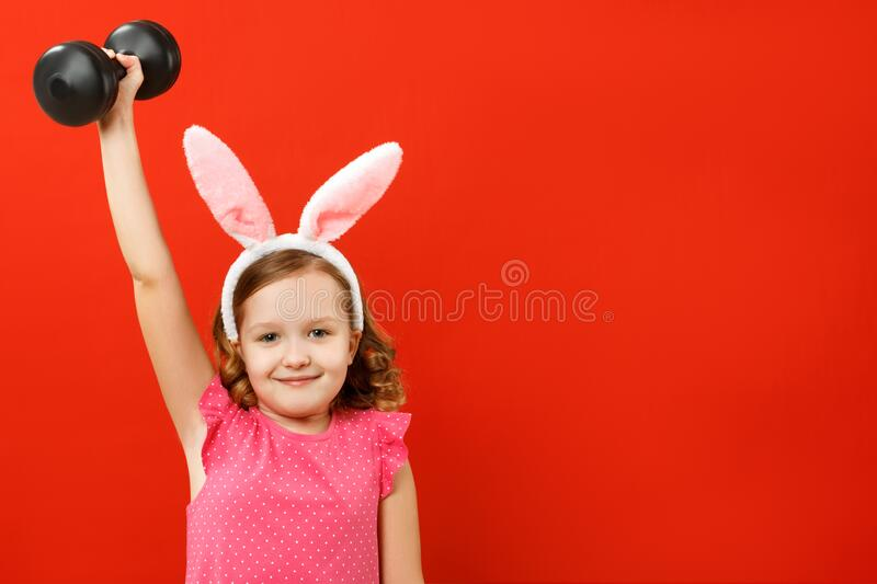 Funny little girl in easter bunny ears raised up a dumbbell. A child on a red background color stock photo