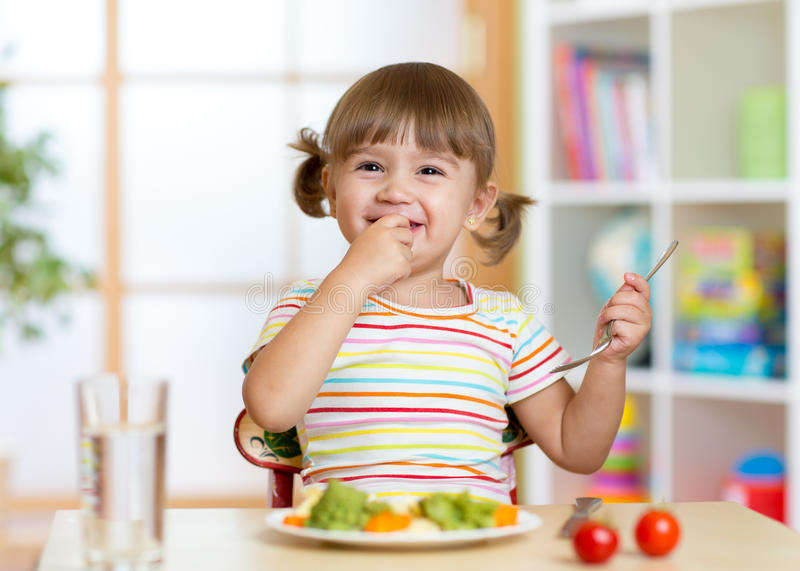 Funny little girl eating healthy food in kindergarten royalty free stock photography