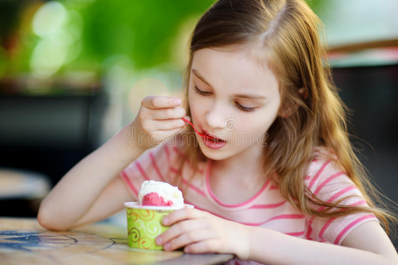 Funny little girl eating ice cream in an outdoor cafe stock images