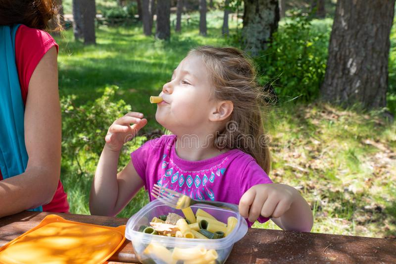 Funny little girl eating pasta from a plastic box next to her mother in a table picnic in countryside. Funny little daughter, four years old blonde girl making royalty free stock photography