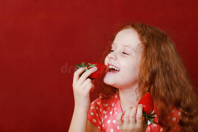 Funny little girl is eating strawberry royalty free stock photo
