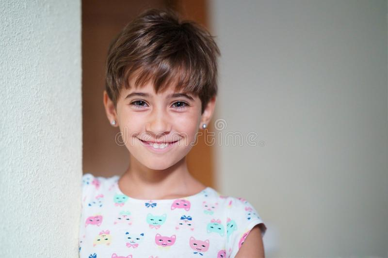 Funny little girl, eight years old, staring smiling to camera. stock photography