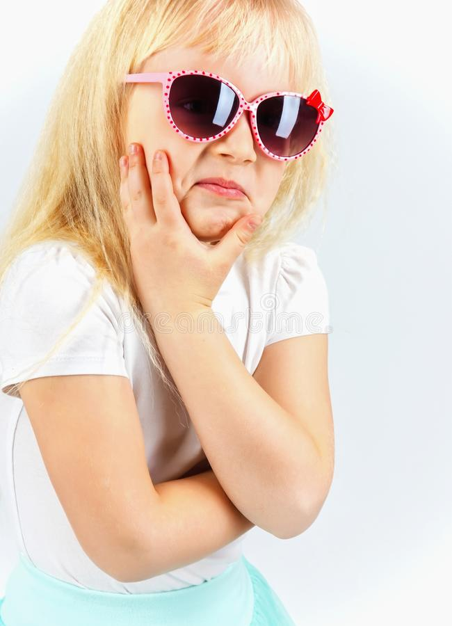Funny little girl with glasses curling showing emotions, makes s. Urprised face, on white background. humor and emotions royalty free stock images