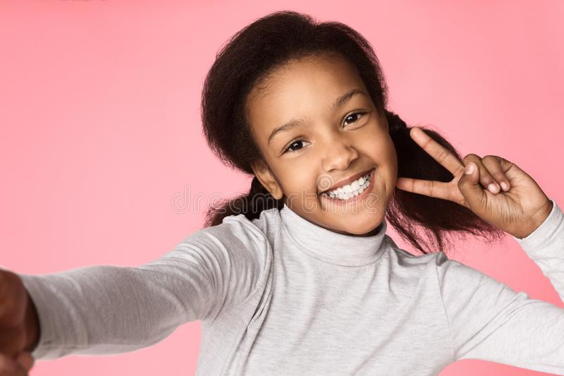 Funny little girl grimacing and taking selfie royalty free stock photography