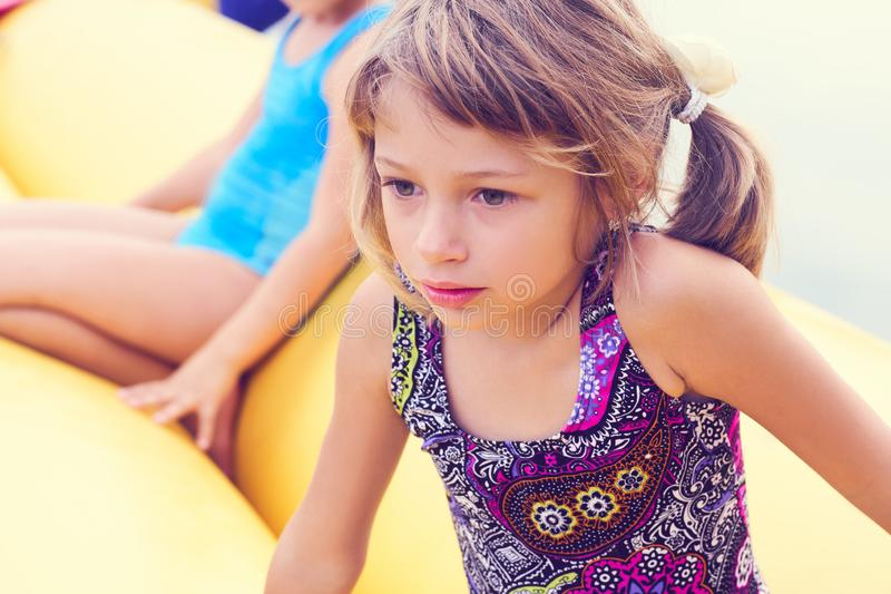 Funny little girl having fun on inflatable rides on the lake. Summer vacation concept stock photo