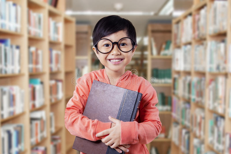 Funny little girl holds literature in the library stock photos