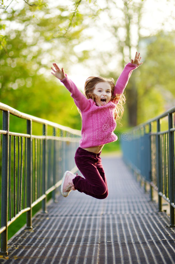 Funny little girl jumping with joy and happines stock image