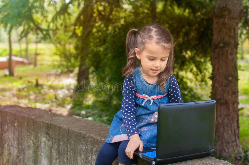 Funny little girl learning with tablet pc in the park royalty free stock photography
