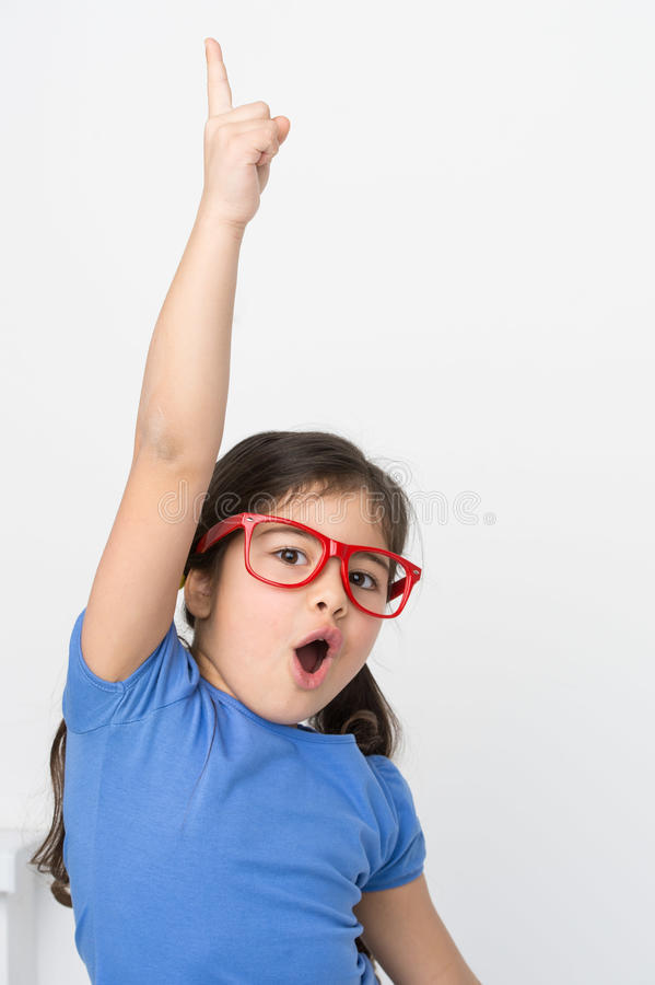Funny little girl lifting hand up. stock photo