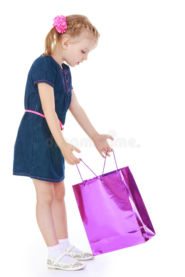 Funny little girl looks in a gift package stock photography