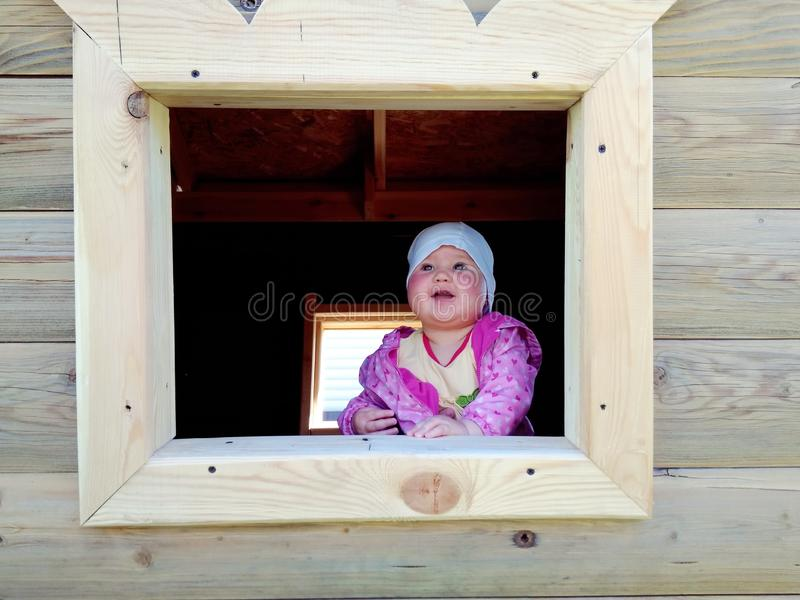 Baby playing in a wooden house royalty free stock photo