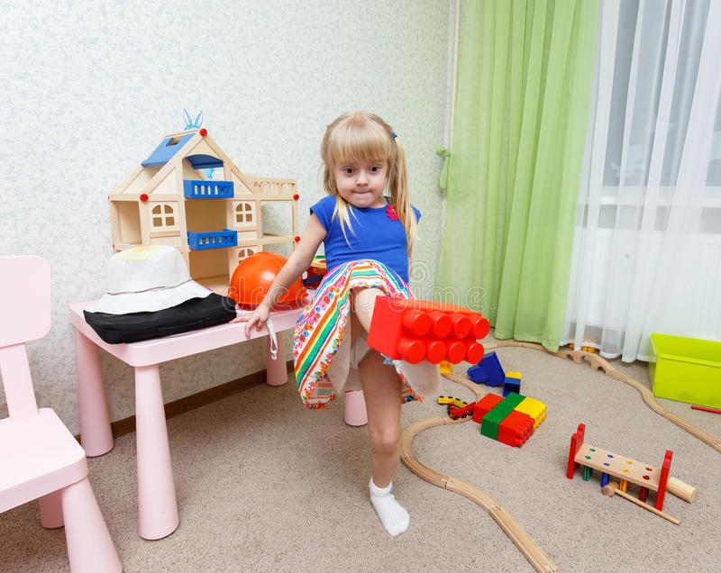 Funny little girl making trick by holding plastic block stock images