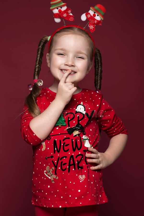 Funny little girl in the New Year`s image, showing different emotions. Photo taken in studio royalty free stock photos