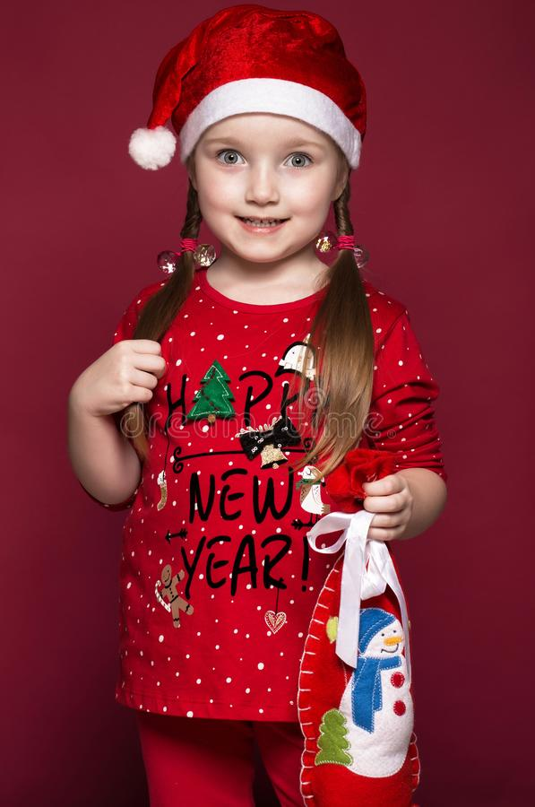 Funny little girl in the New Year`s image, showing different emotions. Photo taken in studio stock image